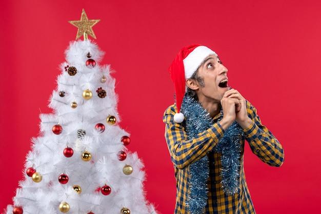 Vista frontal jovem masculino em torno da atmosfera de ano novo na parede vermelha emoção feriado natal