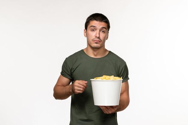 Vista frontal jovem masculino em uma camiseta verde com batata cips assistindo filme na parede branca filme pessoa masculino filme solitário cinema