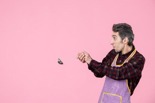 Vista frontal jovem masculino na capa segurando uma colher de sopa de prata no fundo rosa cozinheiro cozinha trabalhador cozinha comida horizontal profissão marido