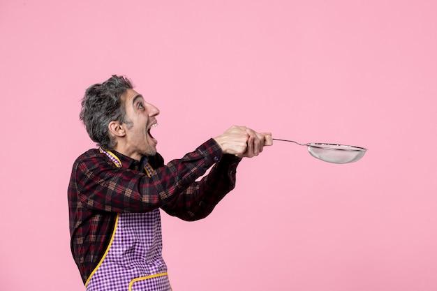 Vista frontal jovem masculino na capa segurando uma peneira no fundo rosa marido trabalhador cozinheiro trabalho cozinha cor horizontal comida
