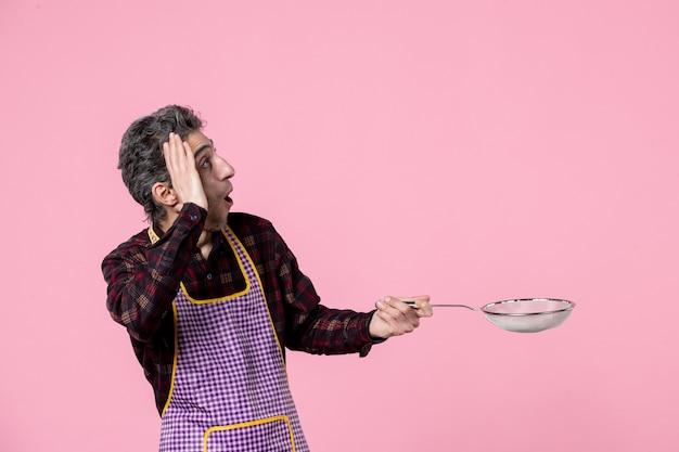 Vista frontal jovem masculino na capa segurando uma peneira no fundo rosa trabalhador cozinheiro trabalho profissão marido horizontal comida cozinha