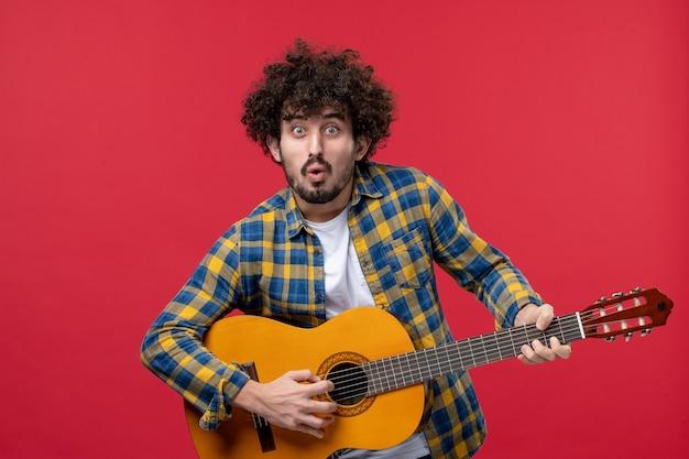 Vista frontal jovem masculino tocando guitarra na parede vermelha concerto banda de cores ao vivo aplausos música tocar músico