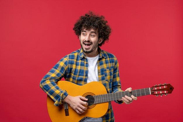 Vista frontal jovem masculino tocando guitarra na parede vermelha concerto cor ao vivo banda de música tocar músico