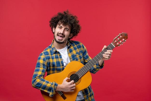 Vista frontal jovem masculino tocando guitarra na parede vermelha concerto cor ao vivo banda musical tocar aplausos do músico