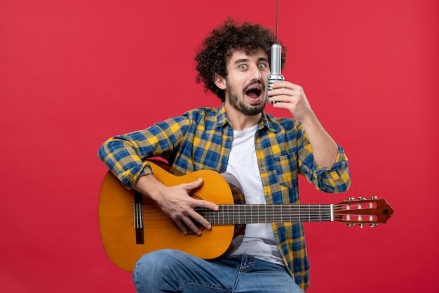 Vista frontal jovem masculino tocando violão e cantando na parede vermelha banda cantor desempenho músico concerto cor música
