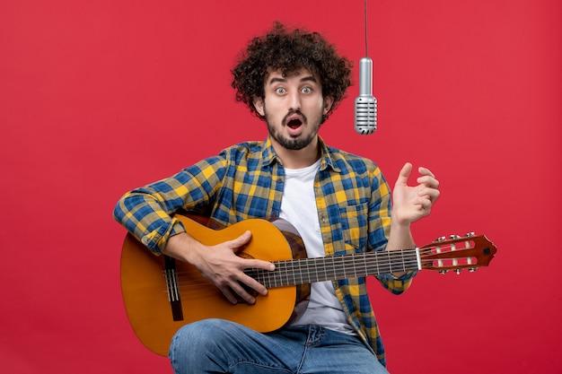 Vista frontal jovem masculino tocando violão e cantando na parede vermelha banda cantor desempenho músico concerto de música ao vivo