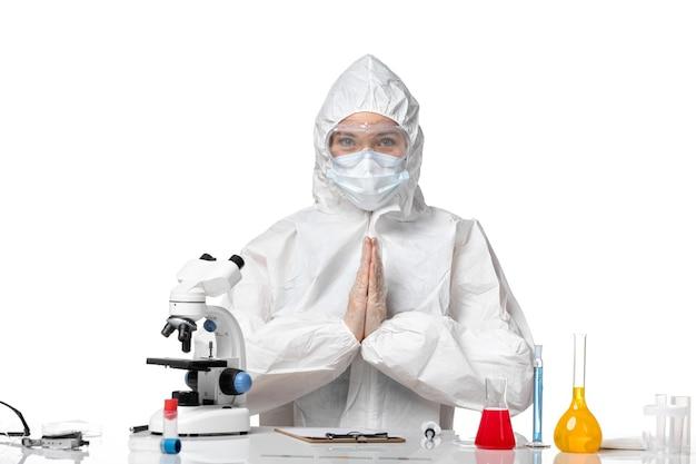 Vista frontal jovem médica em traje de proteção com máscara devido ao cobiçado sentado no fundo branco vírus pandêmico respingo covid-