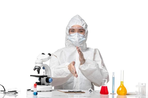 Vista frontal jovem médica em traje de proteção com máscara devido ao covid sentado e sorrindo no fundo branco vírus pandêmico respingo covid-