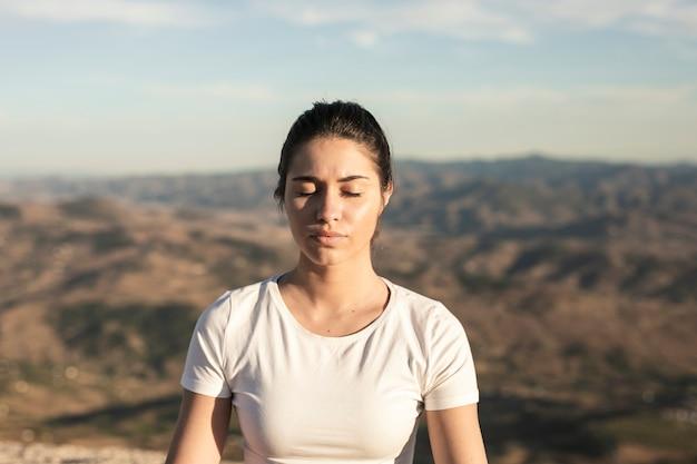 Vista frontal jovem meditação feminina