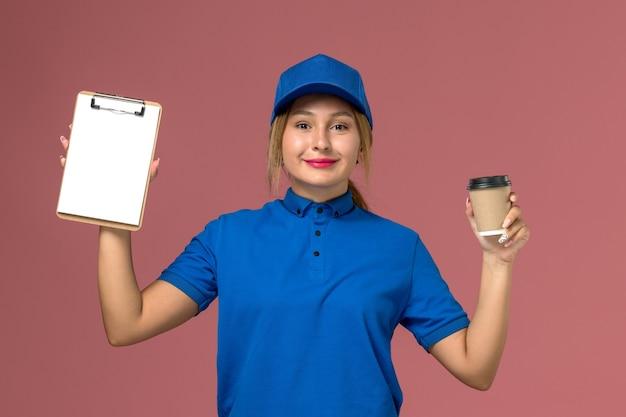 Vista frontal jovem mensageiro de uniforme azul posando segurando a xícara de café e o bloco de notas, trabalhador de trabalho de mulher de entrega de uniforme de serviço
