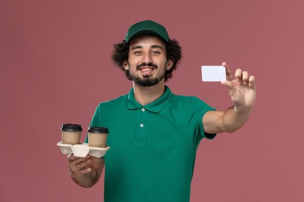 Vista frontal jovem mensageiro masculino em uniforme verde e capa segurando copos de café de entrega e cartão sorrindo no fundo rosa serviço trabalho uniforme entregador trabalhador masculino