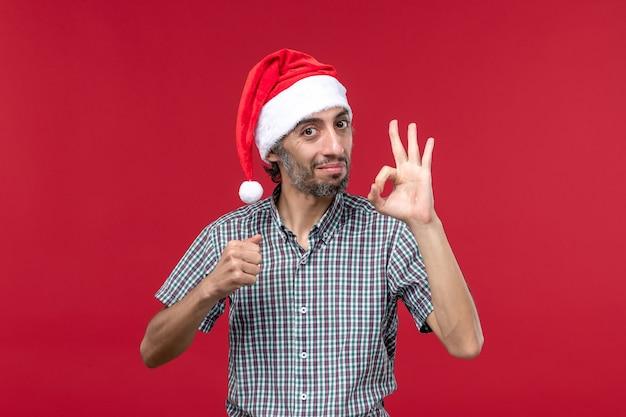 Vista frontal jovem mostrando número na parede vermelha feriado ano novo masculino vermelho