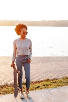 Vista frontal jovem mulher africana segurando um skate