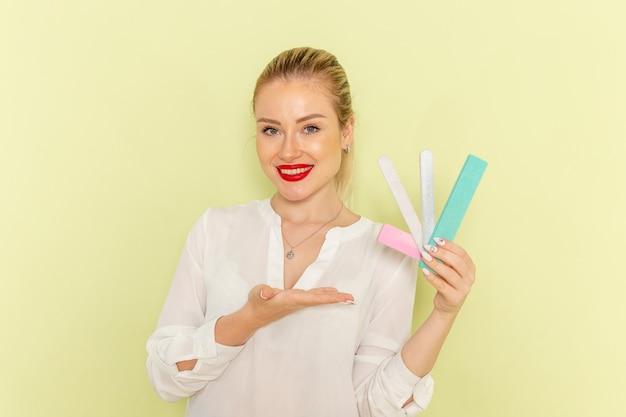 Vista frontal, jovem mulher atraente com camisa branca segurando diferentes acessórios de manicure com um sorriso na superfície verde