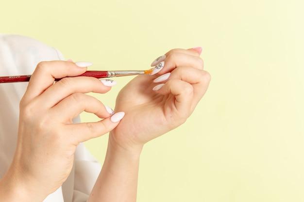 Vista frontal, jovem mulher atraente com camisa branca, trabalhando com as unhas na superfície verde