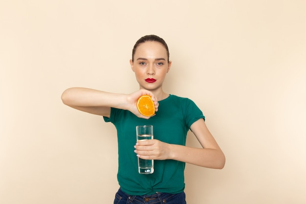 Vista frontal jovem mulher atraente com camisa verde escura e jeans azul segurando água e laranja em bege