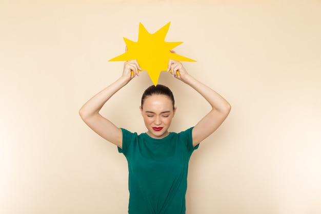 Vista frontal, jovem mulher atraente com camisa verde escura e jeans azul segurando uma placa amarela em bege