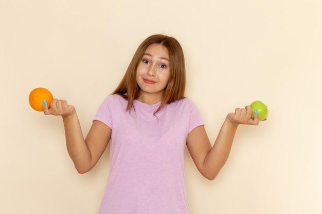 Vista frontal jovem mulher atraente com camiseta rosa e jeans azul segurando laranja e maçã