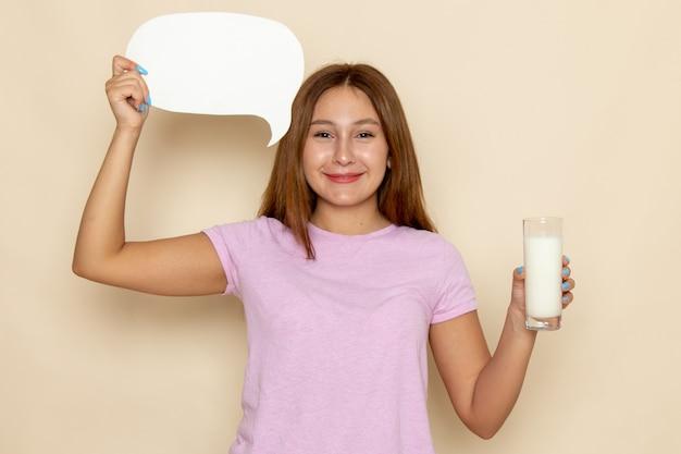 Vista frontal jovem mulher atraente com camiseta rosa e jeans azul segurando leite e cartaz