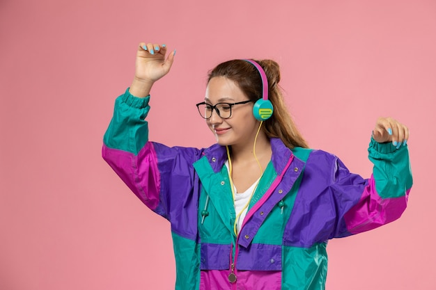 Vista frontal, jovem mulher atraente com casaco colorido de camiseta branca dançando ouvindo música no fundo rosa