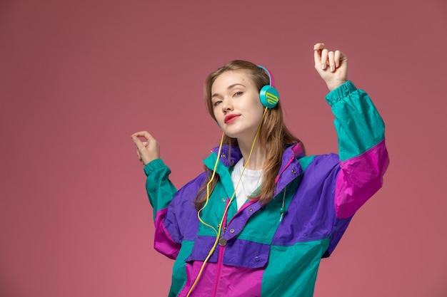 Vista frontal jovem mulher atraente com casaco colorido, ouvindo música e dançando na parede rosa modelo de cor