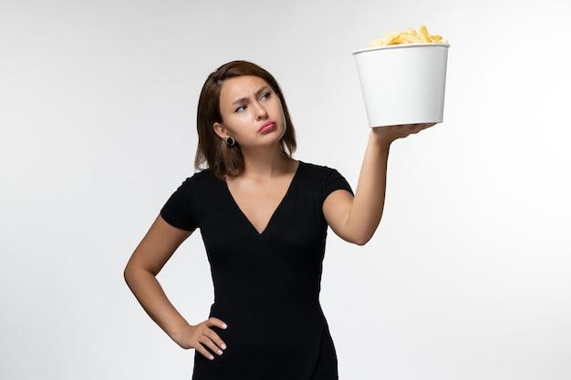 Vista frontal, jovem mulher atraente de camisa preta segurando batata cips assistindo filme na mesa branca