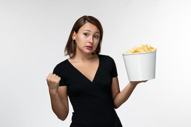 Vista frontal, jovem mulher atraente de camisa preta segurando batatas cips assistindo filme na superfície branca