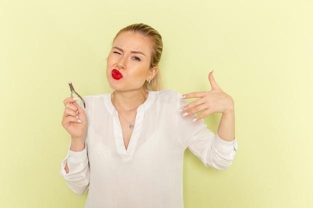 Vista frontal, jovem mulher atraente em camisa branca, consertando as unhas e machucando-se na superfície verde