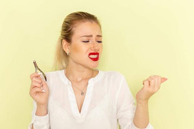 Vista frontal jovem mulher atraente em camisa branca consertando as unhas e se machucando na superfície verde