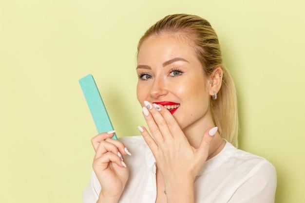 Vista frontal, jovem mulher atraente em camisa branca, fixando as unhas na superfície verde