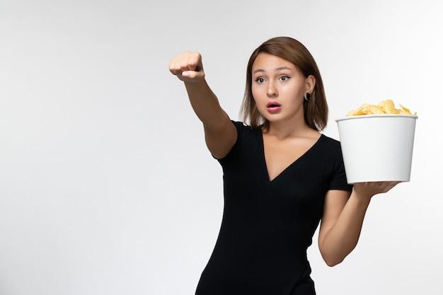 Vista frontal, jovem mulher atraente em camisa preta segurando batatas cips assistindo filme em uma superfície branca clara