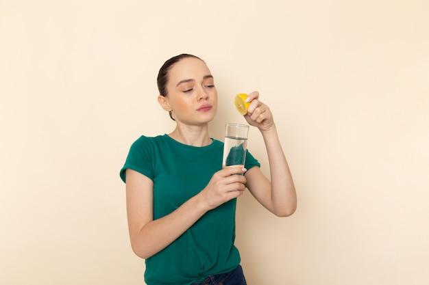 Vista frontal jovem mulher atraente em camisa verde escura e jeans azul espremendo suco de limão em bege