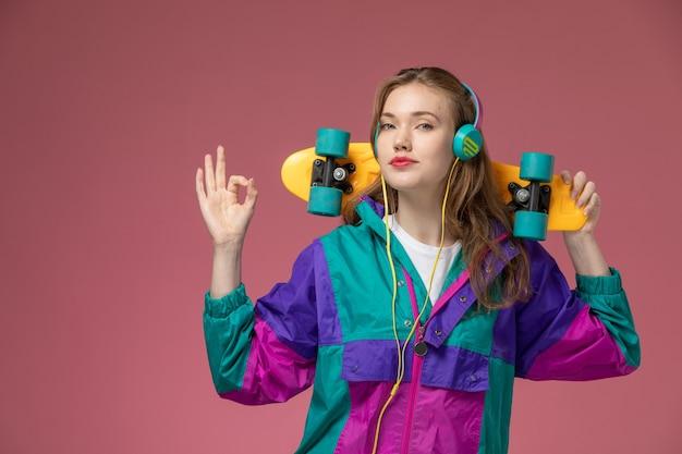 Vista frontal jovem mulher atraente em camiseta branca casaco colorido ouvindo música segurando skate na mesa rosa modelo feminino cor feminina jovem