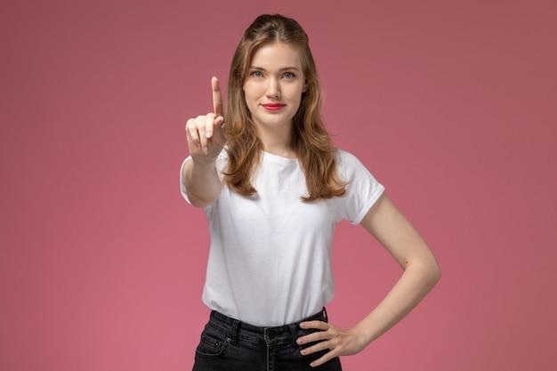 Vista frontal jovem mulher atraente em camiseta branca e calça preta posando com um sorriso na parede rosa modelo feminino pose foto colorida