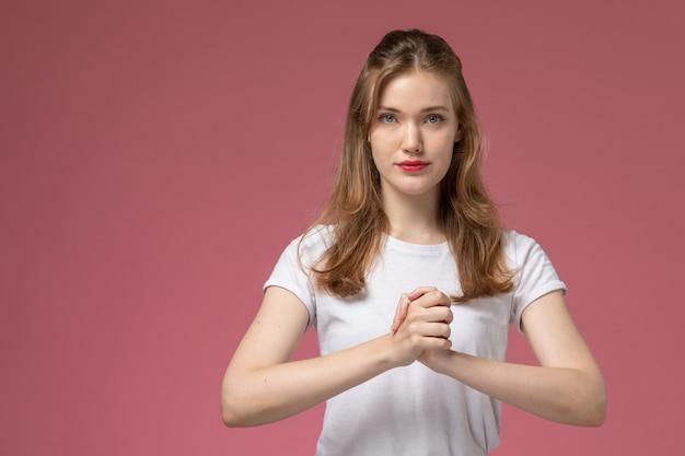 Vista frontal jovem mulher atraente em camiseta branca e calça preta posando na parede rosa modelo feminino pose foto colorida