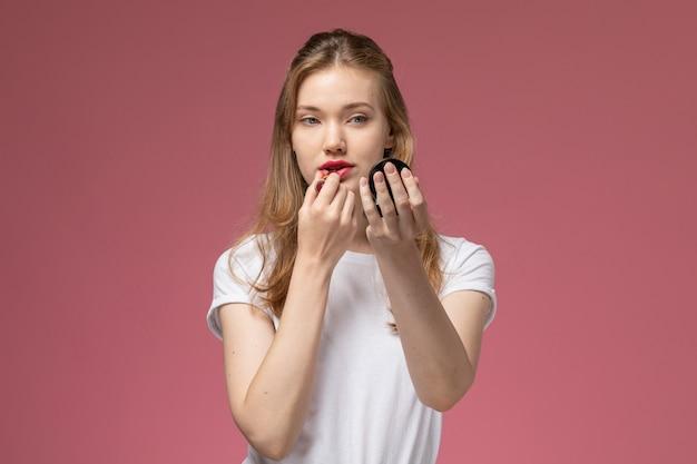 Vista frontal jovem mulher atraente em camiseta branca fazendo maquiagem na parede rosa cor modelo feminino jovem