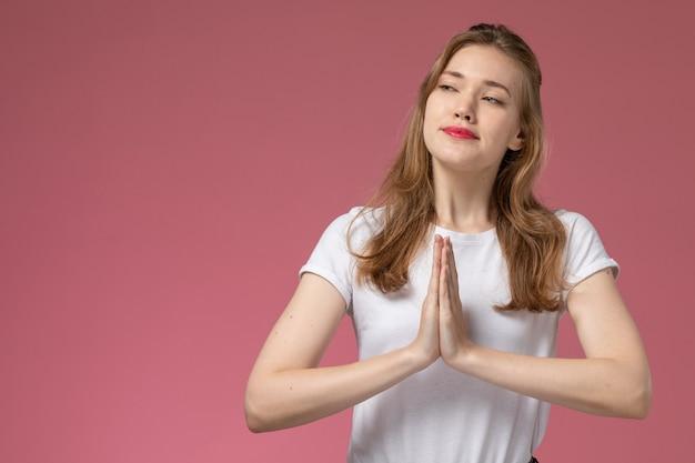 Vista frontal jovem mulher atraente em camiseta branca posando com orações pose na parede rosa modelo feminino pose foto colorida