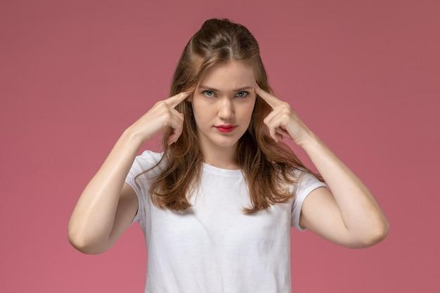 Vista frontal jovem mulher atraente em camiseta branca posando com pensamento pose na parede rosa modelo feminino pose foto colorida