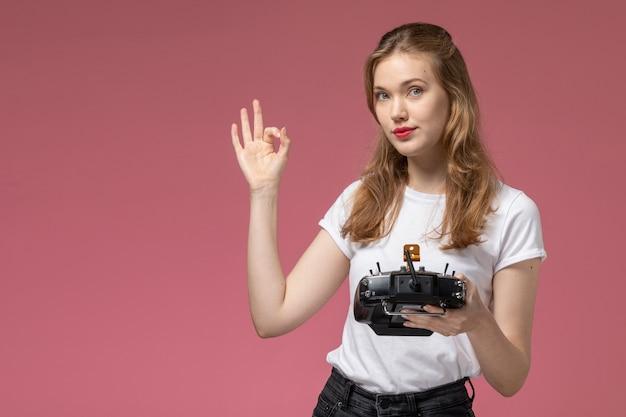 Vista frontal jovem mulher atraente em camiseta branca posando segurando o controle remoto na parede rosa cor do modelo feminino jovem