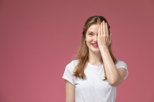 Vista frontal jovem mulher atraente em camiseta branca sorrindo e cobrindo metade do rosto na parede rosa modelo feminino jovem