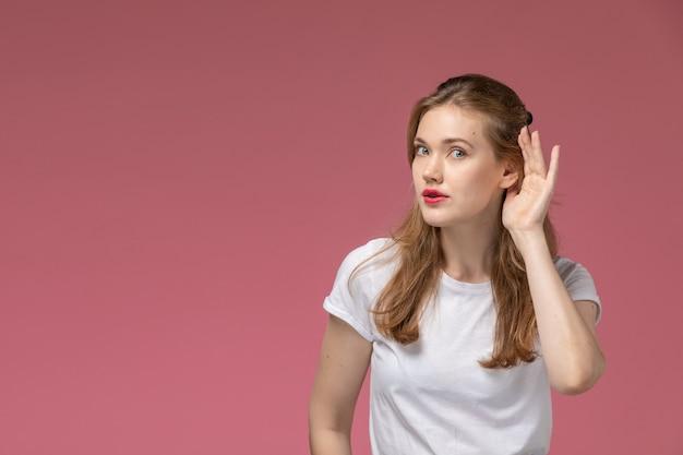 Vista frontal jovem mulher atraente em camiseta branca tentando ouvir na parede rosa modelo feminino pose foto colorida