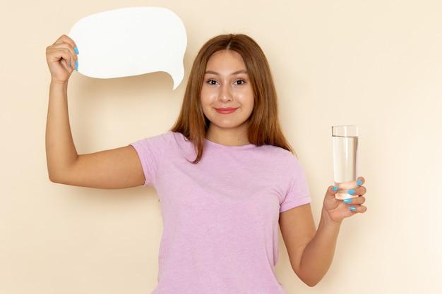 Vista frontal jovem mulher atraente em camiseta rosa e calça jeans segurando um copo de água e uma placa branca