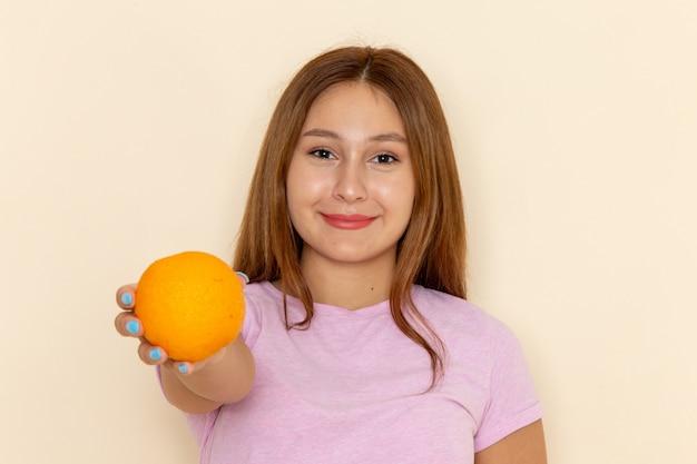 Vista frontal jovem mulher atraente em camiseta rosa e jeans azul segurando laranja e dando
