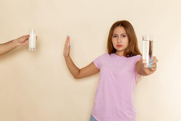 Vista frontal, jovem mulher atraente em camiseta rosa e jeans azul segurando um copo d'água e negando leite