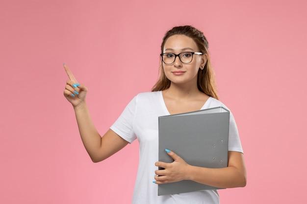 Vista frontal, jovem mulher atraente em uma camiseta branca segurando um documento cinza no fundo rosa