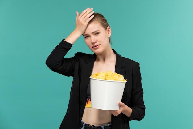 Vista frontal jovem mulher atraente segurando cips e assistindo filme na superfície azul clara