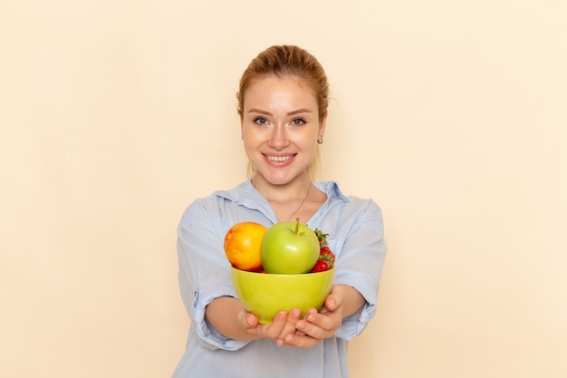 Vista frontal jovem mulher bonita em camisa segurando o prato com frutas e sorrindo na parede creme fruta modelo mulher pose senhora