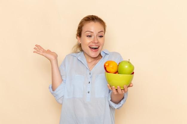 Vista frontal jovem mulher bonita em uma camisa segurando o prato com frutas e sorrindo na parede creme claro frutas modelo mulher pose senhora