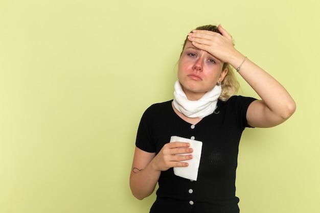 Vista frontal jovem mulher com camisa preta toalha branca em volta da garganta se sentindo muito mal e doente na parede verde doença doença saúde feminina