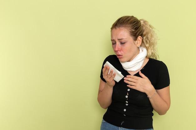 Vista frontal jovem mulher com camisa preta toalha branca em volta da garganta sentindo-se muito doente e doente na parede verde doença doença cor feminina saúde